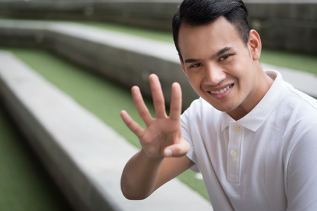 happy man pointing up four finger gesture; smiling friendly man pointing 4 number, number four fingers hand sign; guy points up number four hand sign concept of counting, numbering