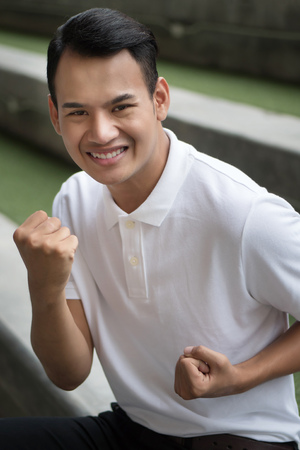 excited man, happy smiling positive man, man showing guts pose; portrait of excited happy smiling strong winning man raising his arms, looking up at you; southeast asian male model
