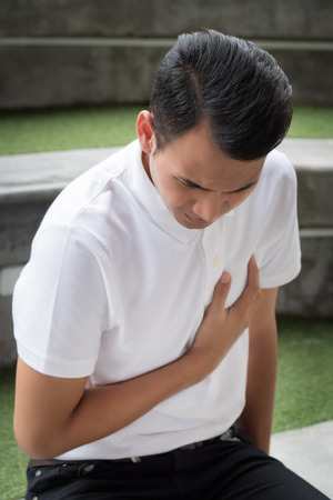 man with heart attack; sick asian man suffering from heart attack or seizure; young adult asian man model, dangerous acute heart attack health care concept