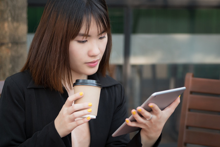 business woman using computer tablet; portrait of businesswoman in formal suit working, holding, looking at her handy mobile computer tablet; asian chinese young adult woman model
