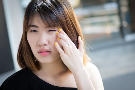 woman suffering from eye allergy; portrait of asian woman with eye irritation, inflammation, red eye problem, concept of optical eye care; young adult asian woman model