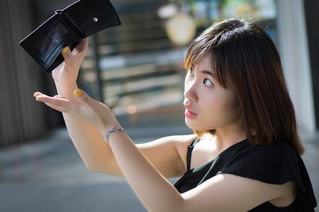 お金のない貧しい女性、空の財布。空の財布、貧しい人々、貧困、破産、財政破綻、失業、信用概念を持たない貧しい女性の肖像画。アジアの若い