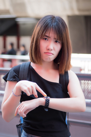 angry woman complaining about late time or delay; portrait of asian woman pointing at wristwatch for the delayed late time; young adult asian woman model