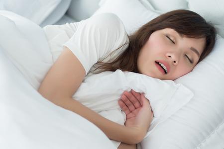 müde, erschöpfte, gestresste Frau, die schnarcht; Porträt einer stressigen, erschöpften Frau, die beim Schlafen auf dem Bett in der Schlafzimmerumgebung schnarcht; medizinisches Konzept für Gesundheit und psychische Versorgung; asiatische erwachsene Frau Modell