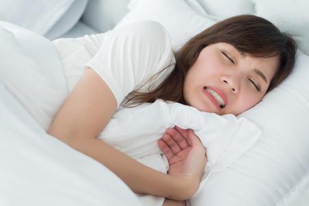 gestresste Frau mit knirschenden Zähnen, Bruxismus-Symptomen; Porträt einer stressigen, erschöpften, müden schlafenden Frau, die vor Stress die Zähne knirscht; medizinisches Konzept für Mund- und Zahnpflege; asiatische erwachsene Frau Modell