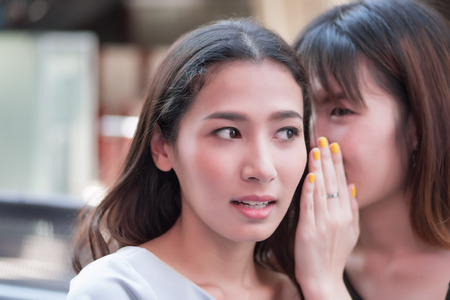 woman gossip getting news information; women chatting, whispering gossip or heresay from her friend; concept of news information transmission or casual social network; asian 20s woman model Stock Photo
