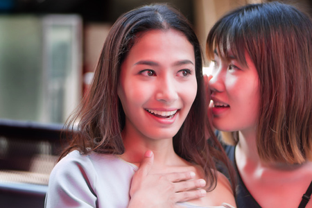 excited happy woman knowing good news; happy smiling or laughing women, being whispered gossip or good news from her friend; concept of good news information transmission; asian 20s woman model Stock Photo