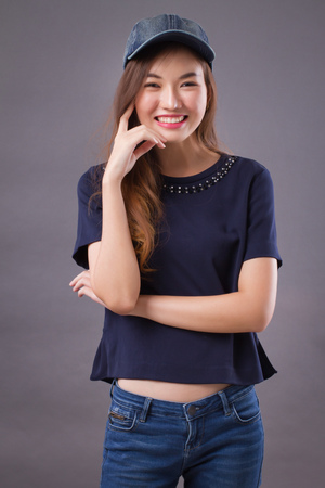 happy asian girl with smiling woman face; portrait of happy, smiling, joyful, cheerful asian woman in casual dress studio isolated; asian chinese young adult woman model Stock Photo - 102969991