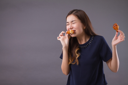 woman eating unhealthy fat fried chicken; portrait of unhealthy girl eating fat fried chicken, fast food; unhealthy eating, dining with high cholesterol fat concept; asian chinese 20s woman model Standard-Bild