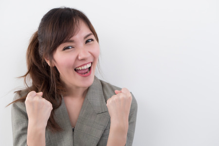 strong winning asian business woman in suit; portrait of strong successful positive excited happy smiling asian businesswoman isolated with guts pose; asian chinese adult woman model, business theme