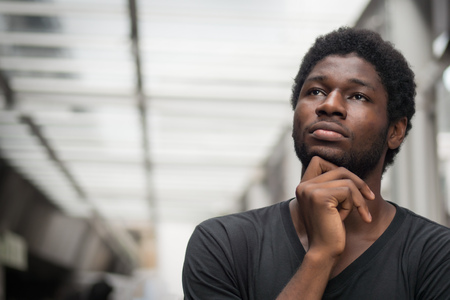 Thoughtful African man thinking; portrait of pensive young adult african man thinking about plan, idea, future, brain storming concept; west African young adult man model
