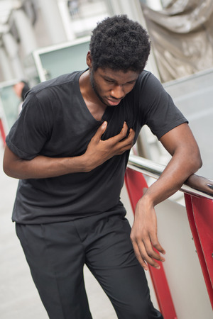 sick african man with heart attack or chest pain; portrait of african man suffering from heart attack, chest pain, health care concept; young adult african man or black man model Stok Fotoğraf