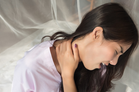 woman with shoulder or neck pain; portrait of asian woman suffering from stiff shoulder, neck bone dislocation, upper spinal injury or pain; body and health care concept; asian young adult woman model Stock Photo