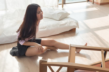 injured woman with hip pain or back injury; portrait of asian woman falling from chair, having pain at her back or hip, concept of wound, bruise, injury from home accident; 20s adult asian woman model