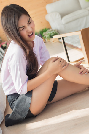 injured woman with knee pain or leg injury; portrait of asian woman falling on floor, having pain at her knee or leg; concept of wound, bruise, injury, pain from accident; 20s adult asian woman model