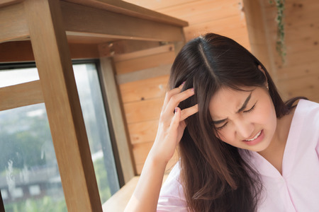 portrait of sick woman with headache; depressed woman suffers from stress, vertigo, dizziness, migraine, hangover; health care and mental health concept; 20s young adult asian woman model Stock Photo