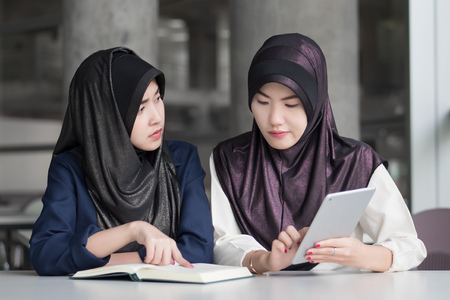 back to school with serious muslim woman college students; portrait of islamic woman students with hijab studying hard in college level education, back to school concept; asian young adult woman model