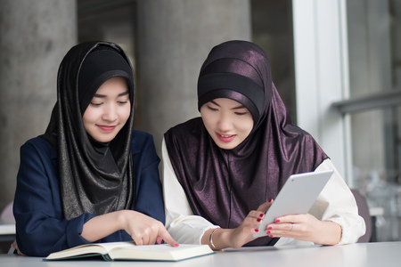 muslim woman college students getting back to school; portrait of happy smiling islamic woman students studying in college education; fall, winter back to school concept; asian young adult woman model