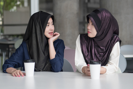 muslim woman talking; islam  or islam women chatting, talking with her friend; asian 20s woman model with hijab or islamic head scarf Stock Photo