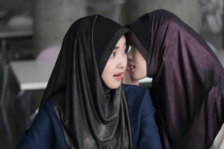 muslim woman gossip getting news information; islamic or islam women chatting, whispering gossip or heresay from her friend; asian 20s woman model with hijab or islamic head scarf