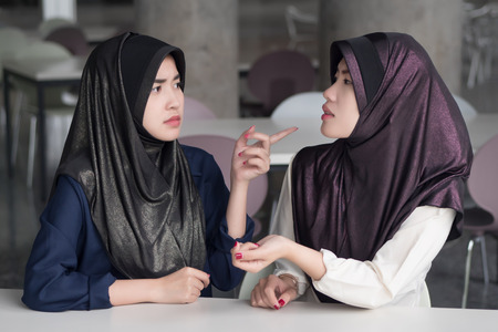 angry, upset, frustrated islam woman arguing; islamic or muslim women arguing with and blaming her friend; asian 20s woman model with hijab or islamic head scarf