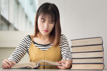 smart woman college student reading books; portrait of focused woman university student studying, researching, reading book in library; asian young adult woman mode Stock Photo