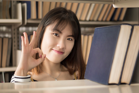 woman college student searching books with accepting ok hand sign; portrait of happy smiling asian woman university student finding book in library and pointing accepting, good, ok hand gesture Stock Photo
