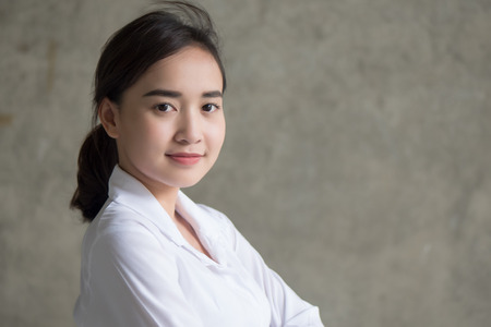 confident happy asian woman in white shirt; portrait of successful happy positive asian woman with confident face expression, proud of success; asian chinese 20s young adult woman model Stock Photo