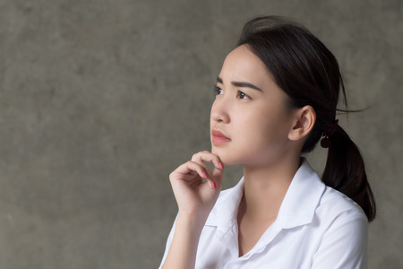 thoughtful woman thinking, planning; portrait of serious, pensive asian woman looking up, thinking, finding good idea or decisive plan; adult asian chinese thai woman model Stock Photo