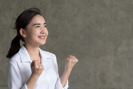 strong winning asian woman in shirt; portrait of strong successful positive excited happy smiling asian business woman, smart casual style, success concept; asian chinese thai young adult woman model
