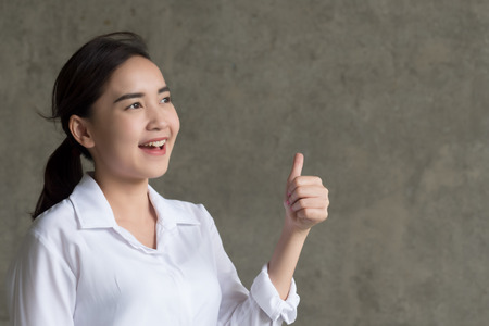 successful girl pointing thumb up; portrait of cheerful smiling woman pointing up approving, yes, ok, good, thumb up gesture, success concept; asian chinese thai 20s woman young adult model