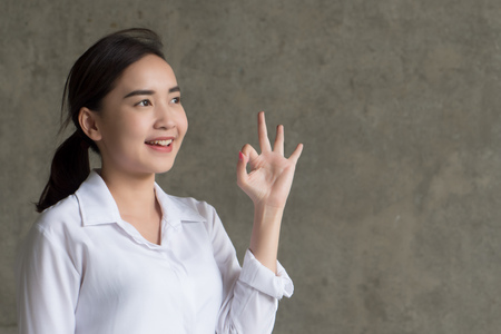 successful girl pointing ok or okay hand sign; portrait of happy smiling woman pointing up approving, yes, good, ok or okay gesture, success or winning concept; asian chinese woman young adult model