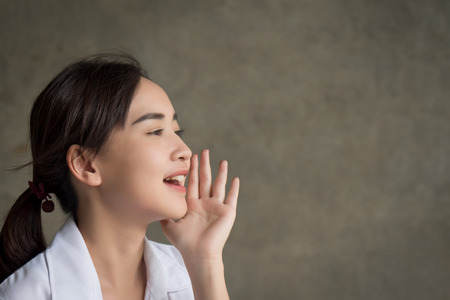 A portrait of happy smiling Asian woman shouting or screaming to blank space; harsh and loud noise shouting communication concept Stock Photo