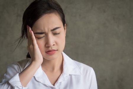 portrait of stressed woman with migraine headache; sick woman suffers from migraine, vertigo, dizziness, hangover, headache; health care concept; young adult asian woman model Stock Photo