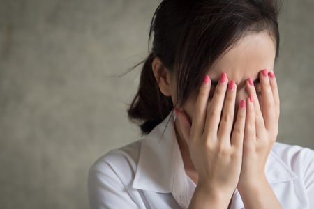 stressed unhappy crying woman doing face palm or face-palm gesture; portrait of frustrated, sad, failed asian woman cries with sadness, failure, frustration, bad news; asian woman young adult model