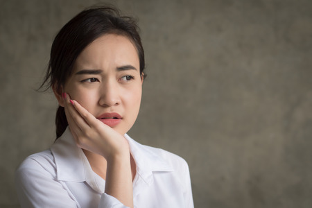 woman with toothache; sick asian woman suffering from toothache, tooth decay, tooth sensitivity, cavity, dental care concept; young adult asian woman model Stock Photo