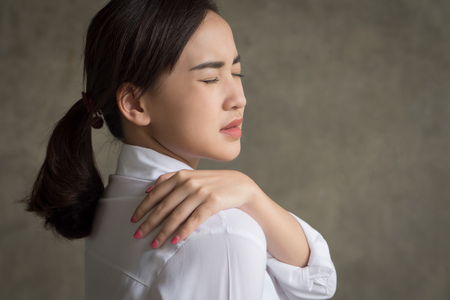 woman with shoulder or neck pain; portrait of asian woman suffering from shoulder or neck pain, stiffness, injury, chronic bone or muscle injury concept; asian young adult woman health care model