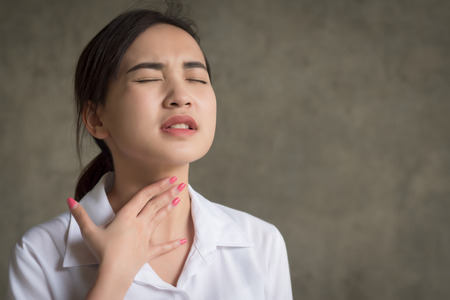 sick woman with sore throat portrait; sick asian woman with sore throat, cold, flu, contagious disease, health care concept; young adult asian woman model