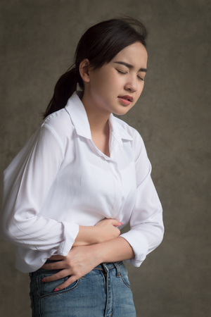 woman with stomach ache; sick woman suffering from stomachache, menstrual period cramp, abdominal pain, food poisoning, gastritis, acid reflux; asian young adult woman health care model Stock Photo