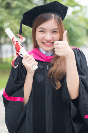 happy smiling graduated woman university student points thumb up; portrait of smiling woman student with graduation diploma or college degree giving thumb up gesture; asian 20s young adult woman model