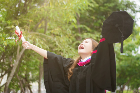 happy successful smiling cheerful woman university student graduating; portrait of diploma or college woman student with graduation degree, education success concept; asian 20s young adult woman model