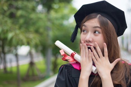 excited graduated woman university student looks and points up with surprise; portrait of surprised woman student with graduation diploma or college degree; asian 20s young adult woman model Stock Photo