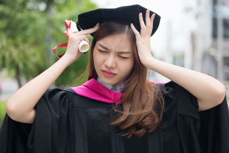 unhappy, stressed woman university student graduating; portrait of diploma or college woman student with graduation degree with headache stress, hard education concept; asian young adult woman model Stock Photo