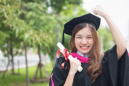 happy successful smiling woman university student graduating; portrait of diploma or college woman student with graduation degree, education concept; asian 20s young adult woman model