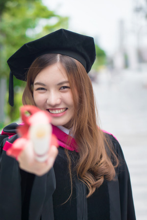 happy graduating woman university student points up; portrait of college successful smiling woman student with graduation degree, education pointing, showing concept; asian 20s young adult woman model