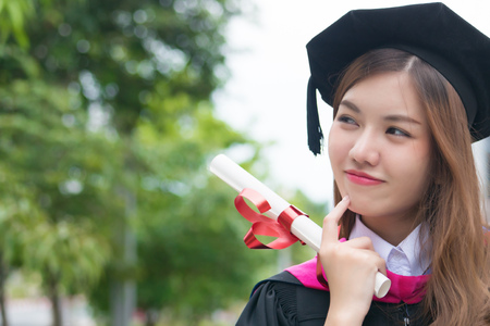 happy smiling graduated woman university student looks and points up; portrait of diploma or college woman student with graduation degree looking up and thinking; asian 20s young adult woman model Stock Photo