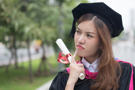 serious graduated woman university student looks and points up; portrait of diploma or college woman student with graduation degree looking up and thinking; asian 20s young adult woman model