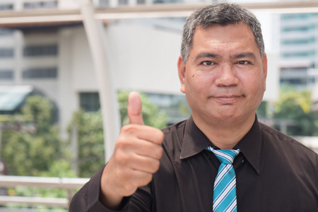 thumb up from successful old business man Foto de archivo