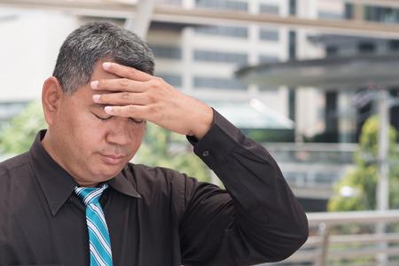 sick old senior man suffers from headache, vertigo, dizziness Stock Photo