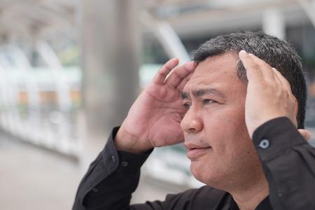 sick old senior man suffers from headache